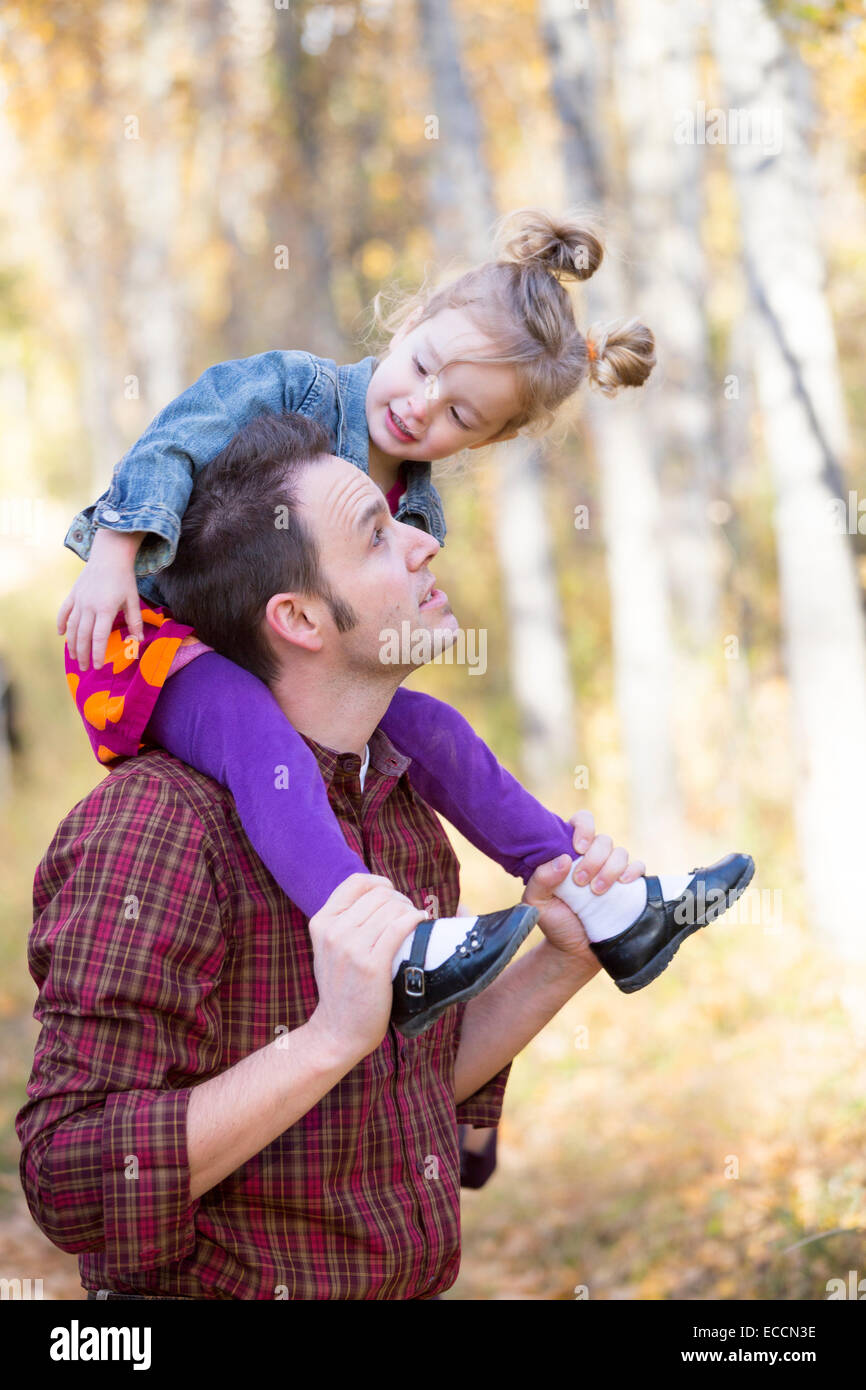 A father and his three year old daughter play during a fall time photo session in Kalispell, Montana. - Stock Image