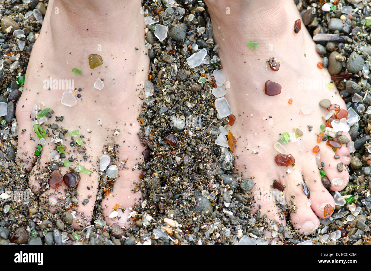 A mans feet are covered in glass from the handfuls of beach glass that wash ashore at Glass Beach in Fort Bragg, - Stock Image
