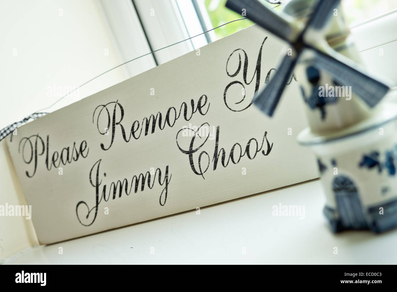 A cute vintage sign on a window sill, proclaiming the play on words, please remove your Jimmy Choos, - Stock Image
