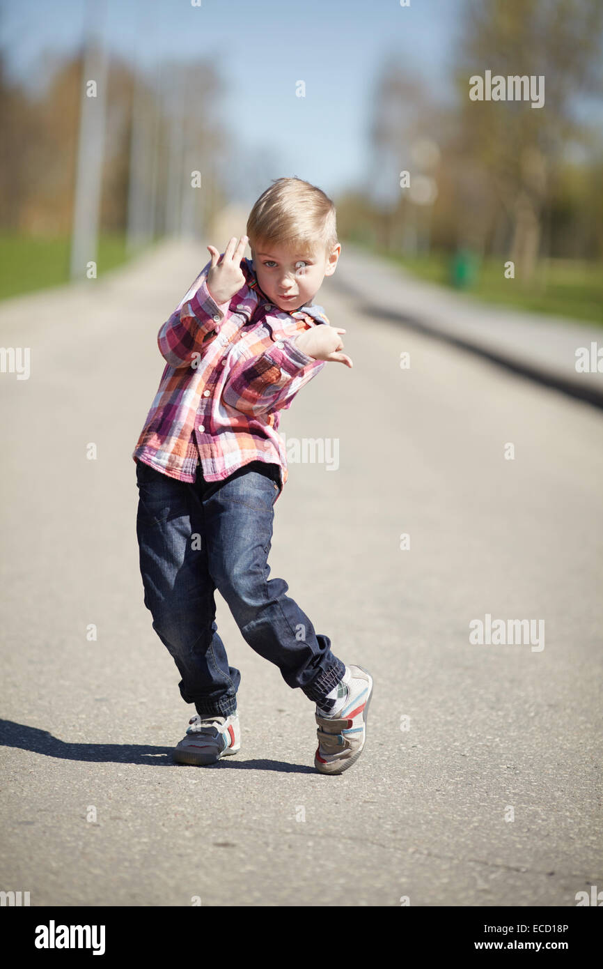 little boy grimacing on the street in april - Stock Image