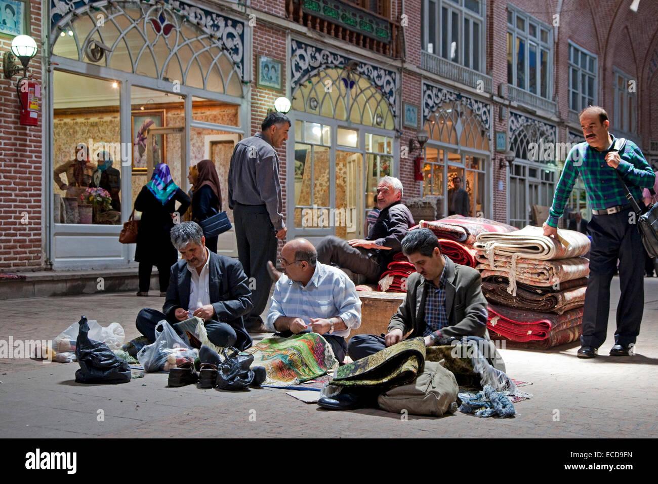 Iranian men repairing carpets in the old historic bazaar of the city Tabriz, East Azerbaijan, Iran - Stock Image