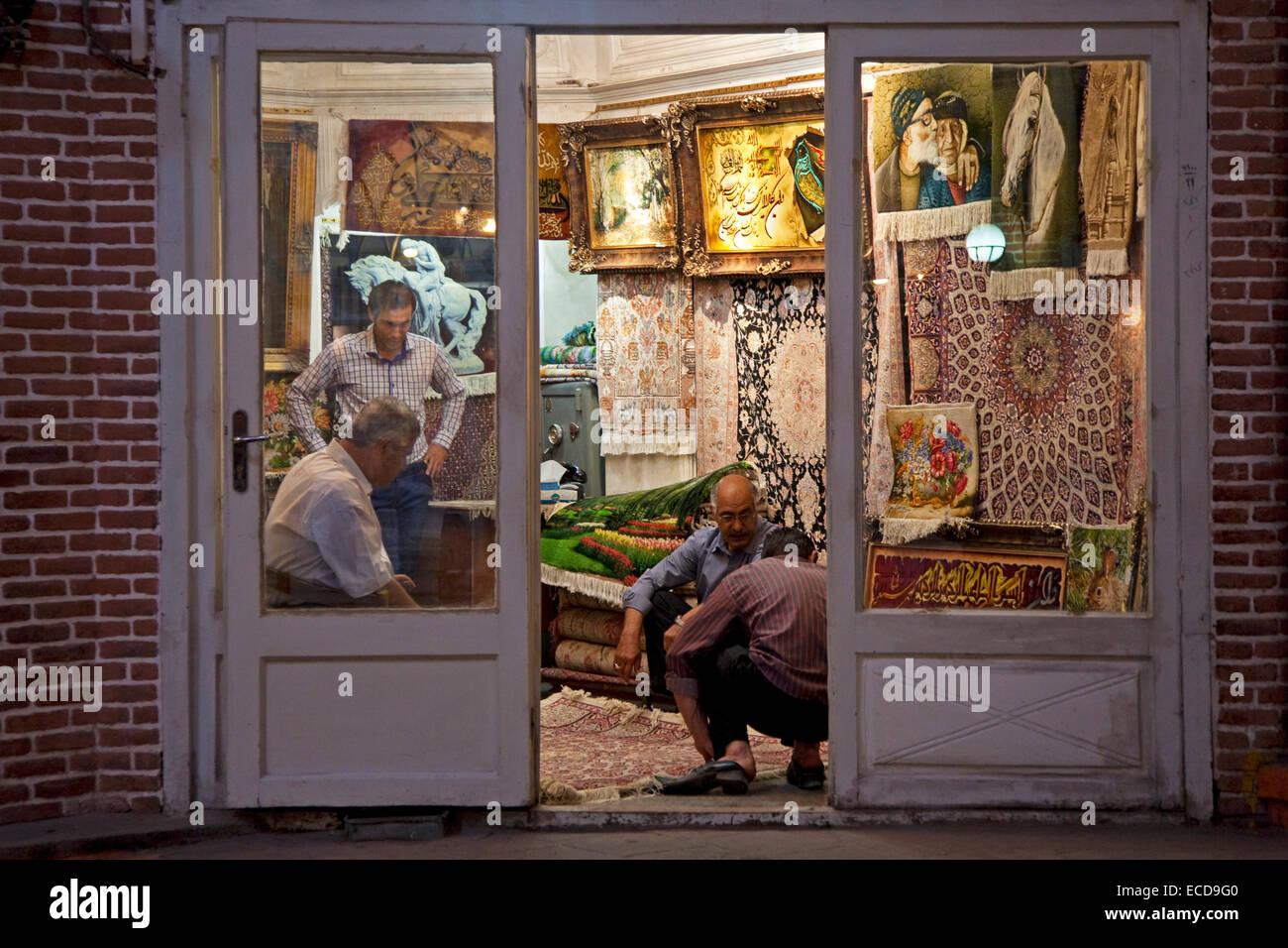 Iranian vendor selling carpets in carpet store in the old historic bazaar of the city Tabriz, East Azerbaijan, Iran - Stock Image