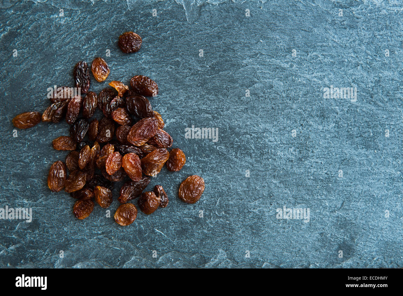 Closeup on raisins on stone substrate - Stock Image