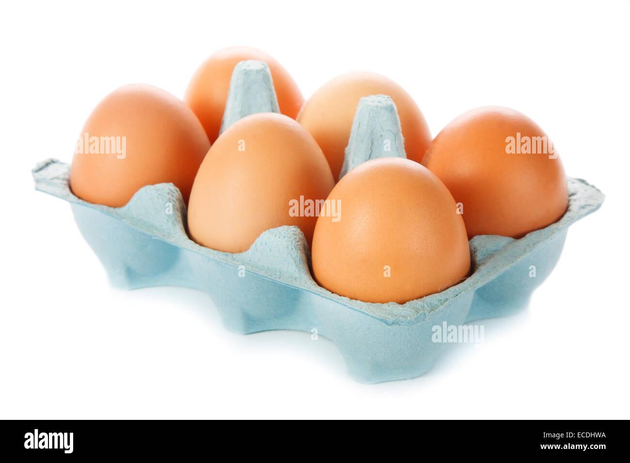 Cardboard egg box and six eggs - Stock Image