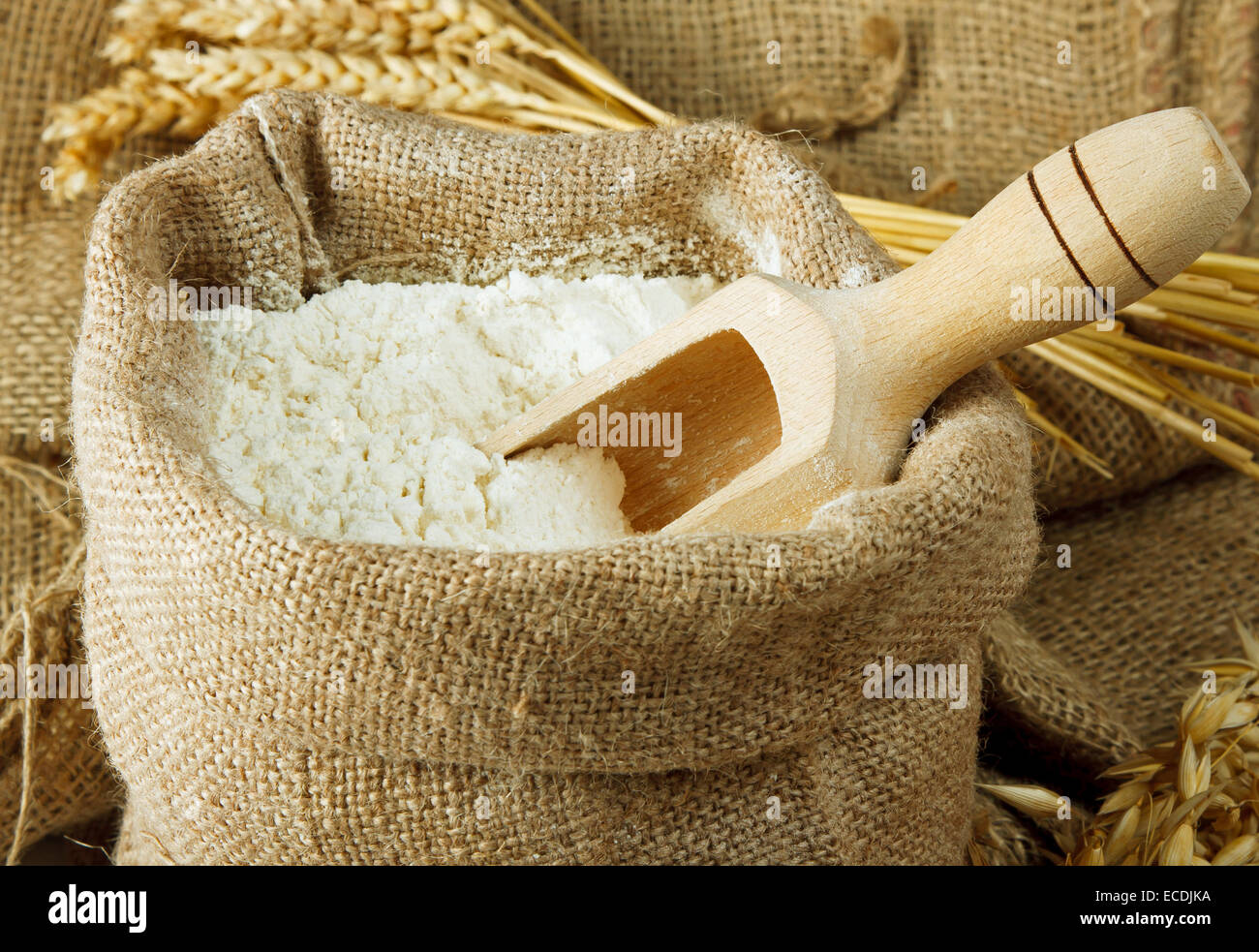 Flour in burlap bag and wooden spoon - Stock Image