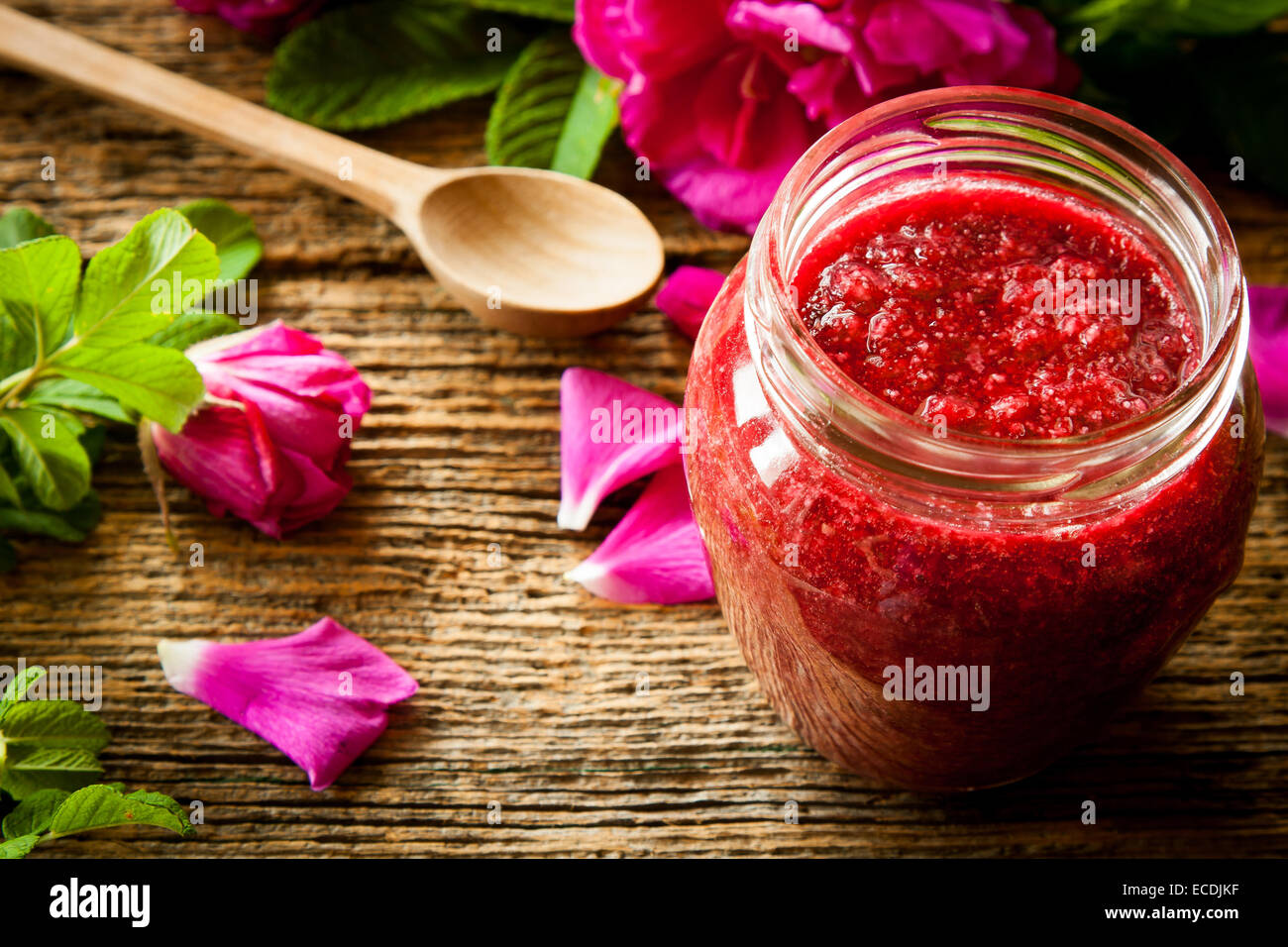 Homemade jam made from damascus petal rose on wooden table. Focus on jar - Stock Image