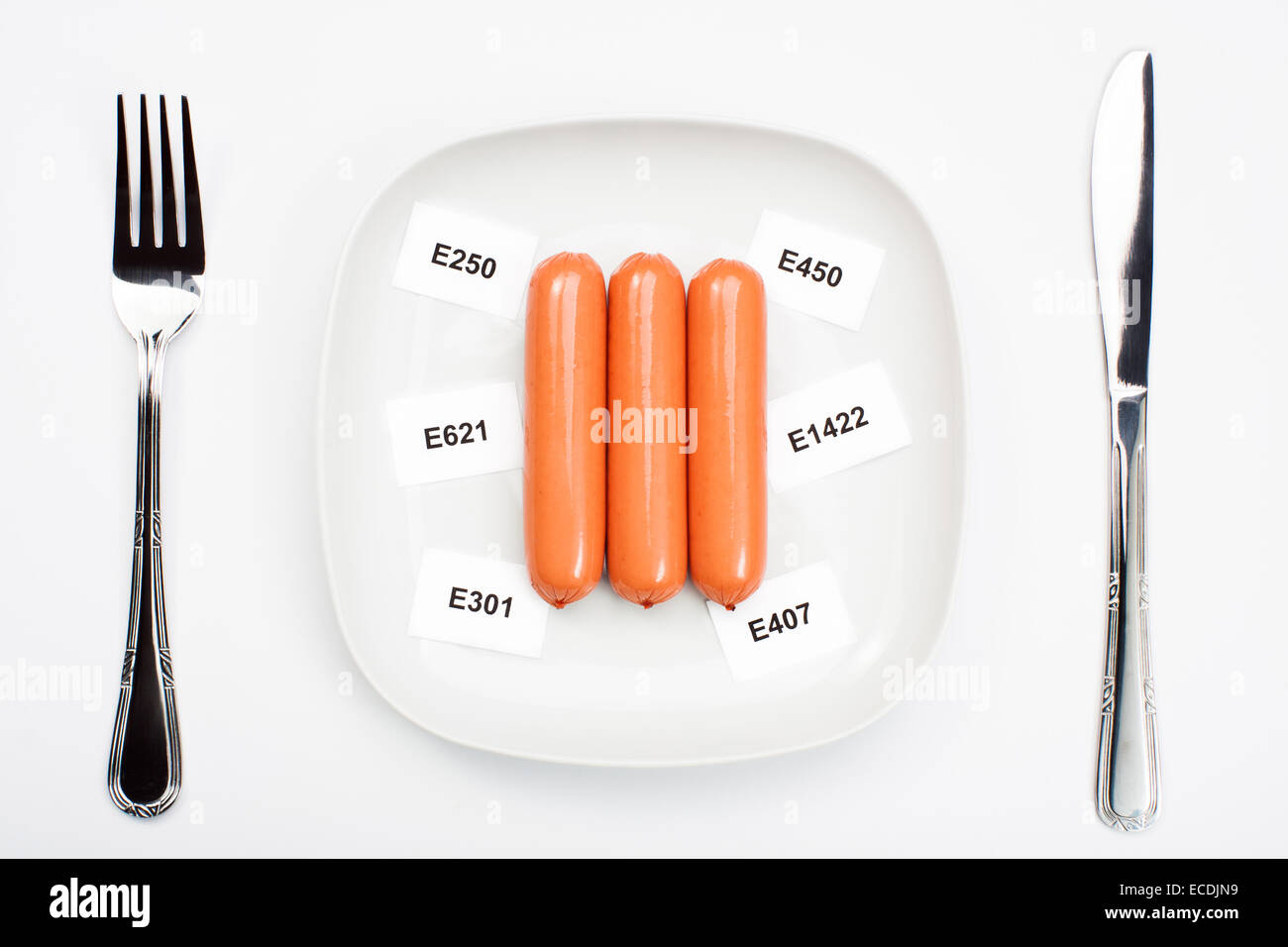 Unhealthy food concept - chemical additives in food. Sausages on plate - Stock Image