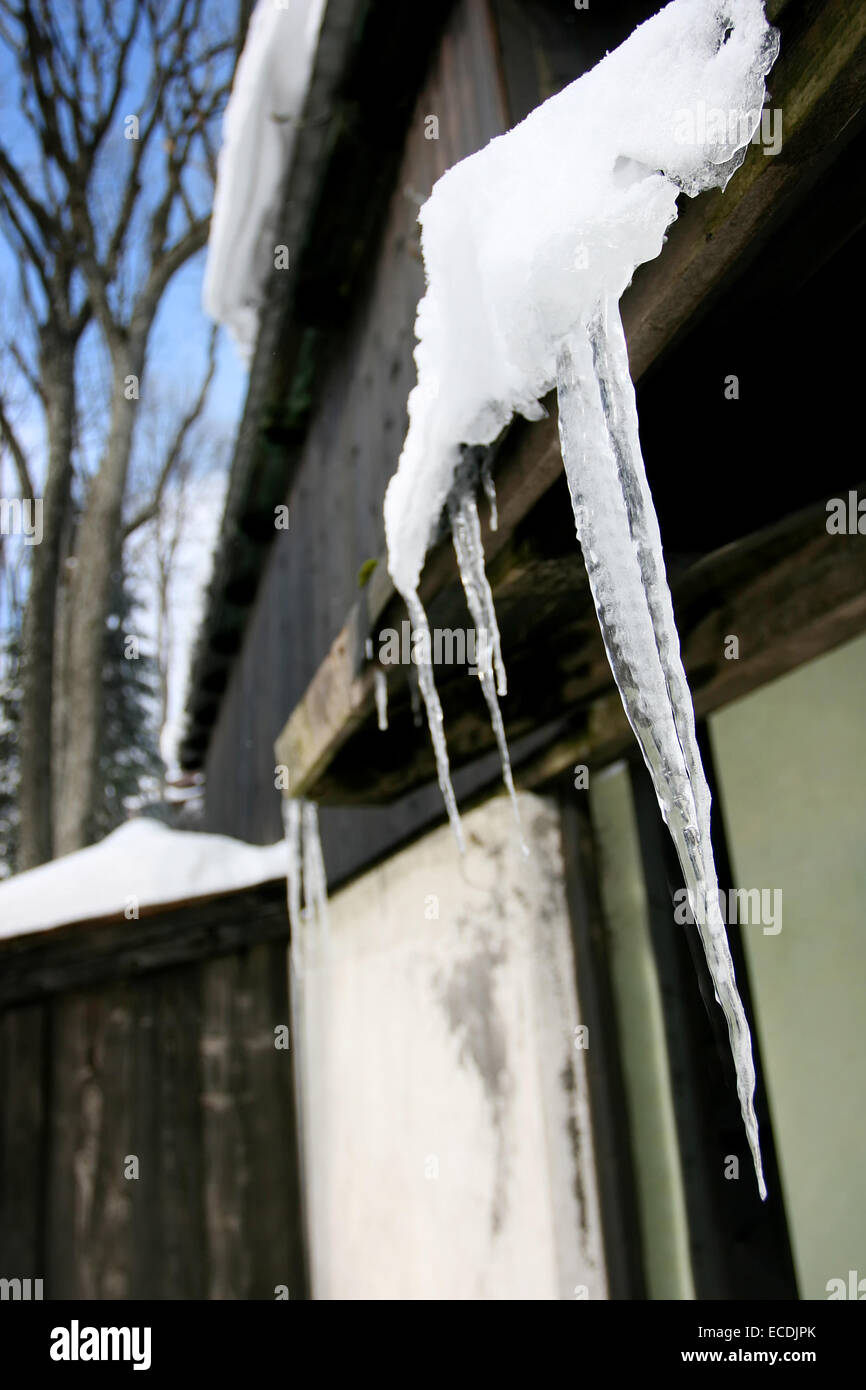 A close up of icicles on wooden house roof. - Stock Image