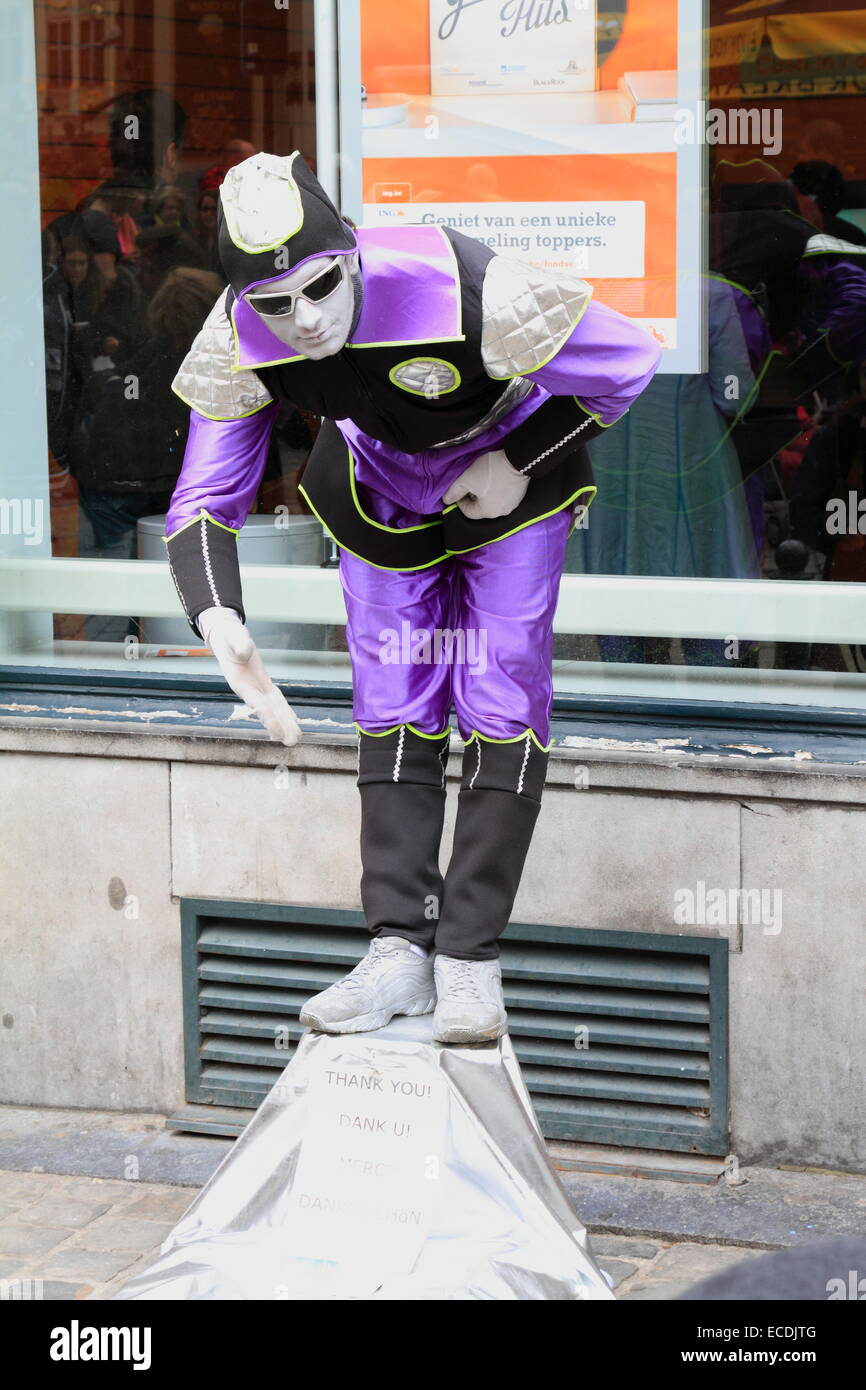 Street mime performer man in violet dress and white painted face. Brussels, Belgium - Stock Image
