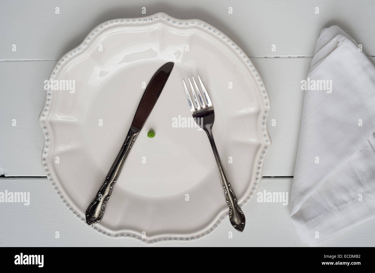Weight loss new year's concept - single pea on a plate - Stock Image