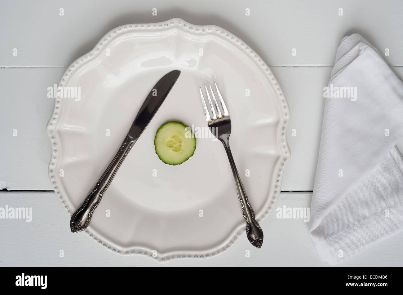 Weight loss new year's concept - single cucumber slice on a plate - Stock Image