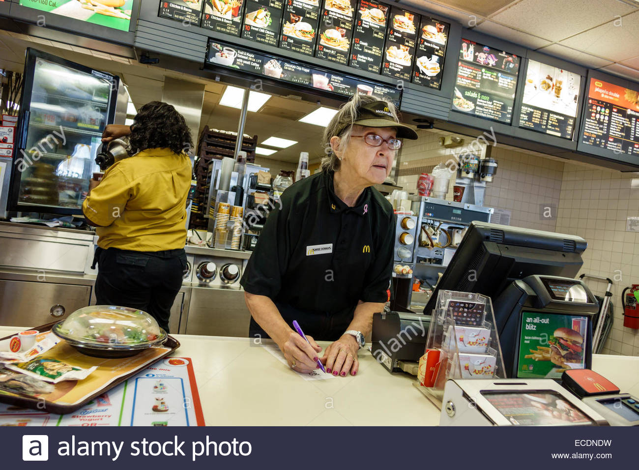 Springfield Illinois McDonald's fast food restaurant counter senior woman employee working uniform - Stock Image