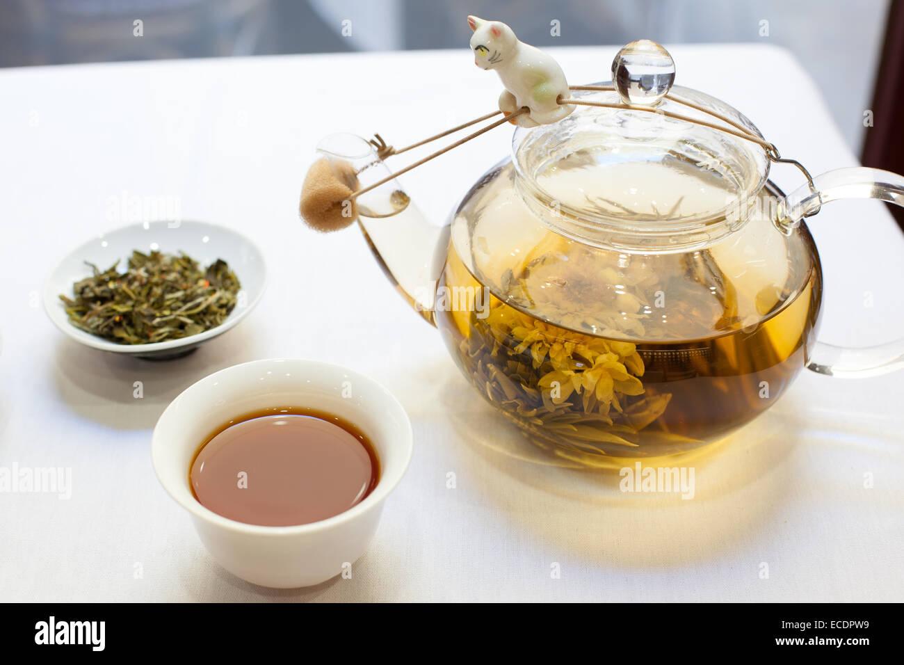 Cup of tea, loose leaf tea, and glass tea pot on white tablecloth - Stock Image