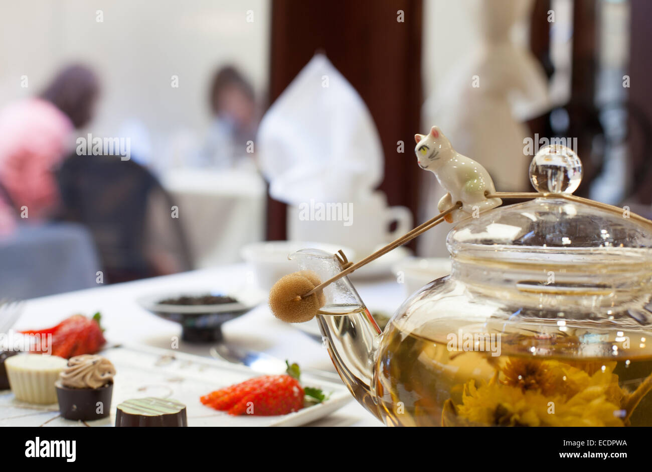 Tea party table with blooming tea glass tea pot and chocolates - Stock Image