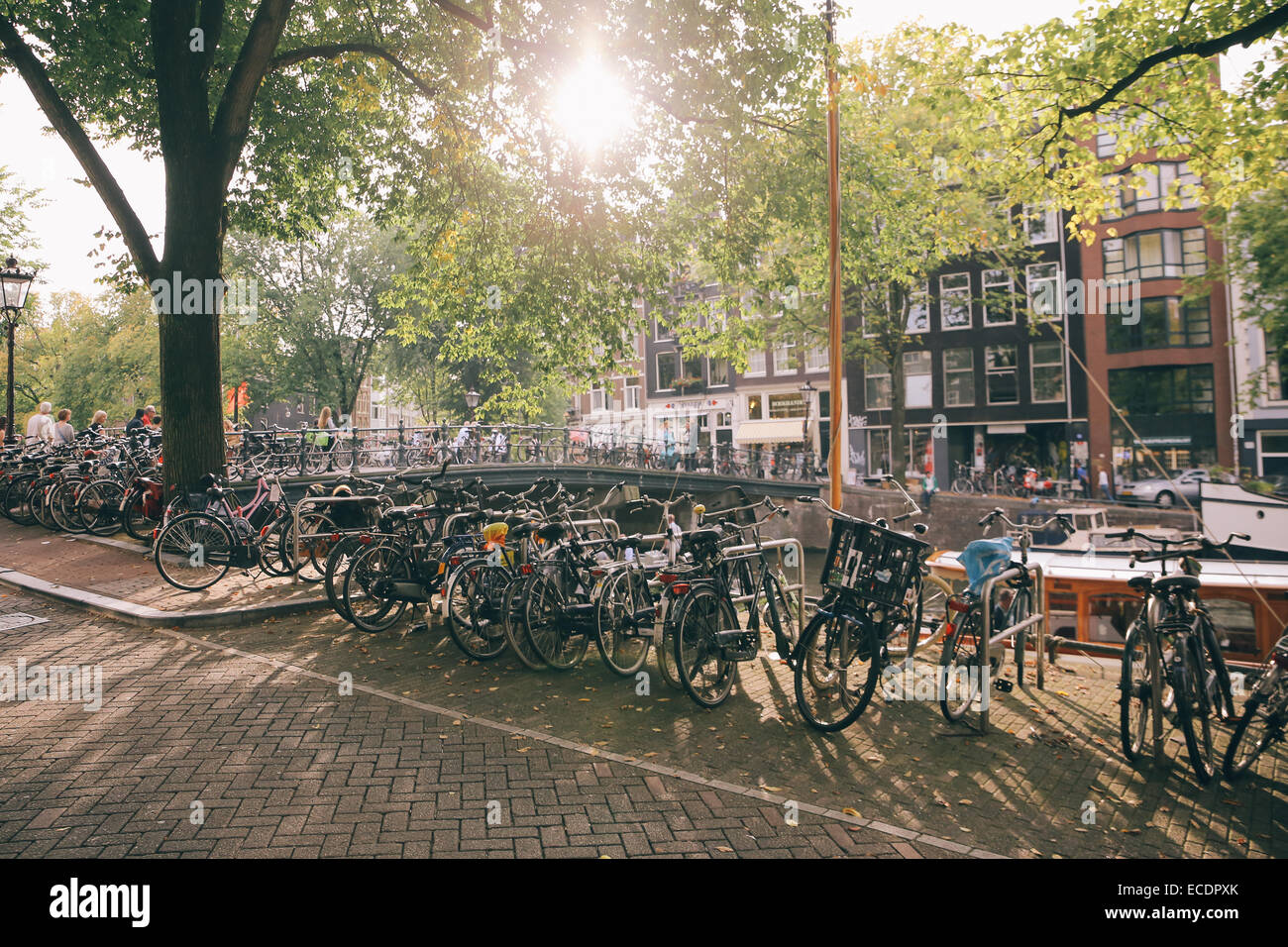 amsterdam bicycles bikes canal day sun flare - Stock Image