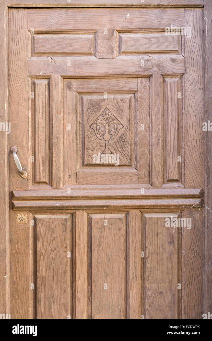 Old brown run-down religious decorated wooden door - Stock Image
