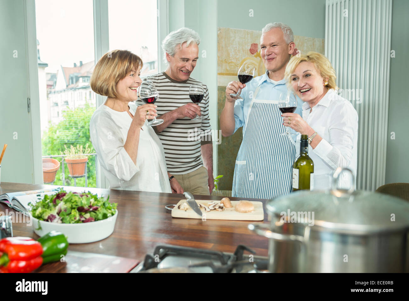 Four senior friends kitchen cooking drinking wine - Stock Image