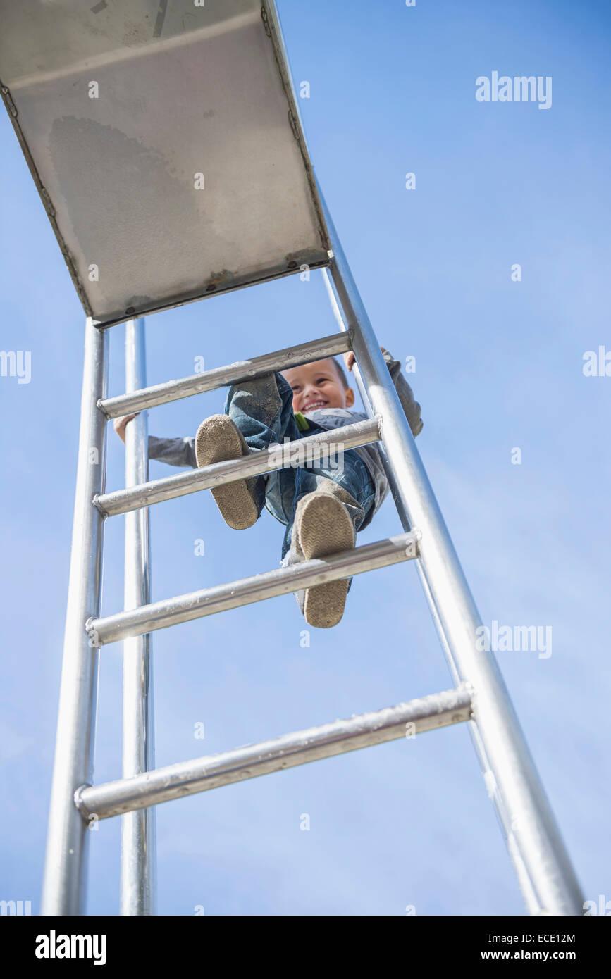 small boy smiling climbing slide ladder playground - Stock Image