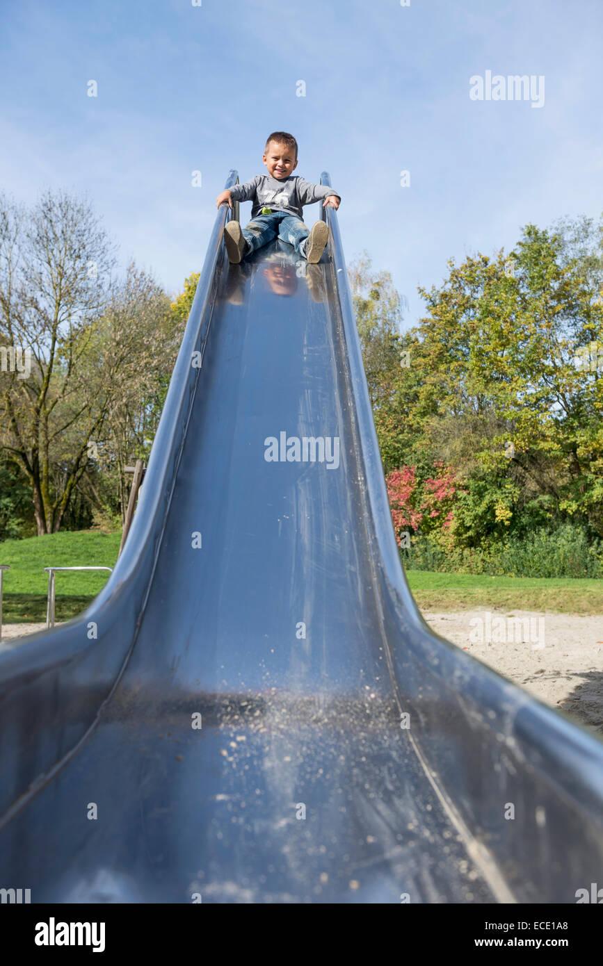 Playground slide small young boy sliding - Stock Image