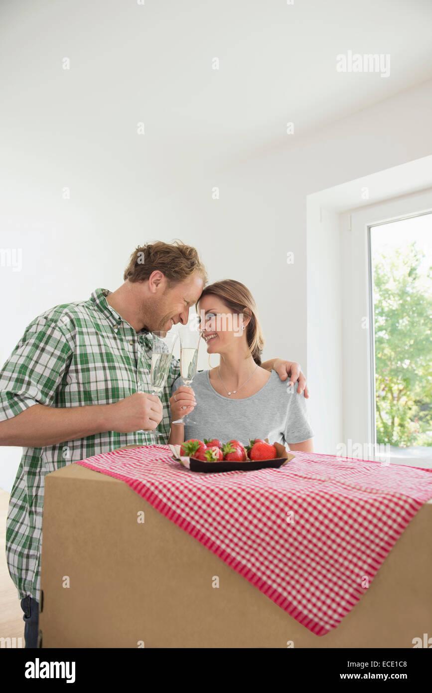 Man woman celebrating new house wine - Stock Image