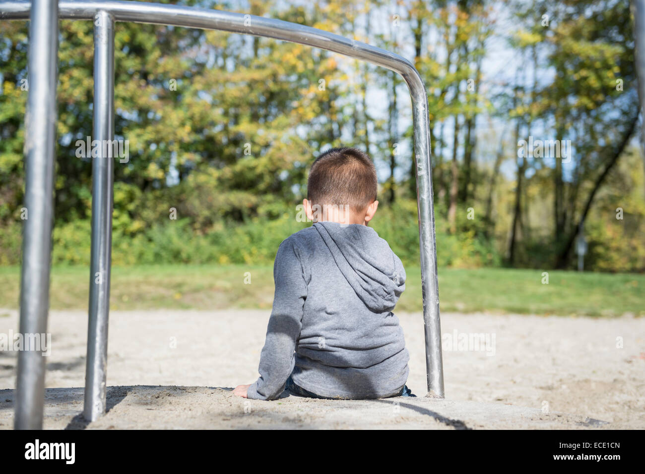 Small lonely boy sitting alone in playground - Stock Image