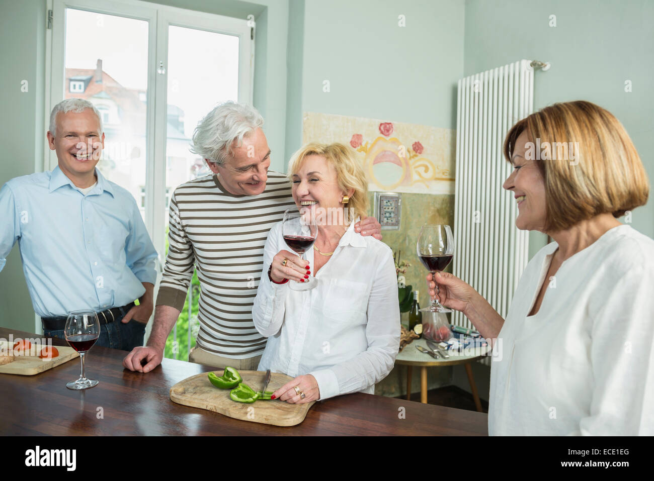 Senior group friends preparing lunch drinking wine - Stock Image