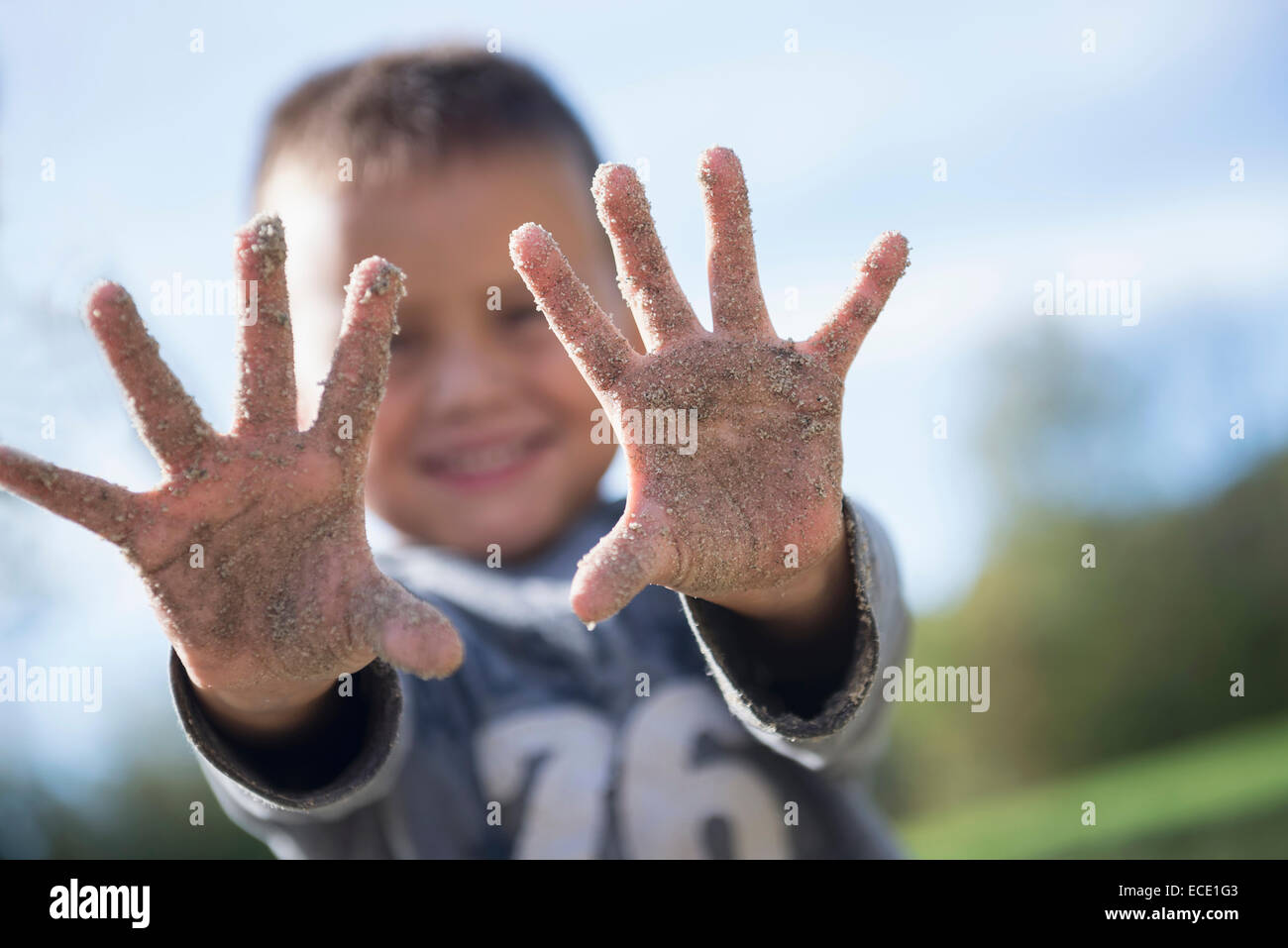 Small boy showing hands covered sand playground - Stock Image