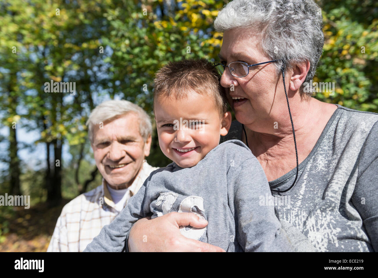 Grandparents young small boy happy sitting - Stock Image