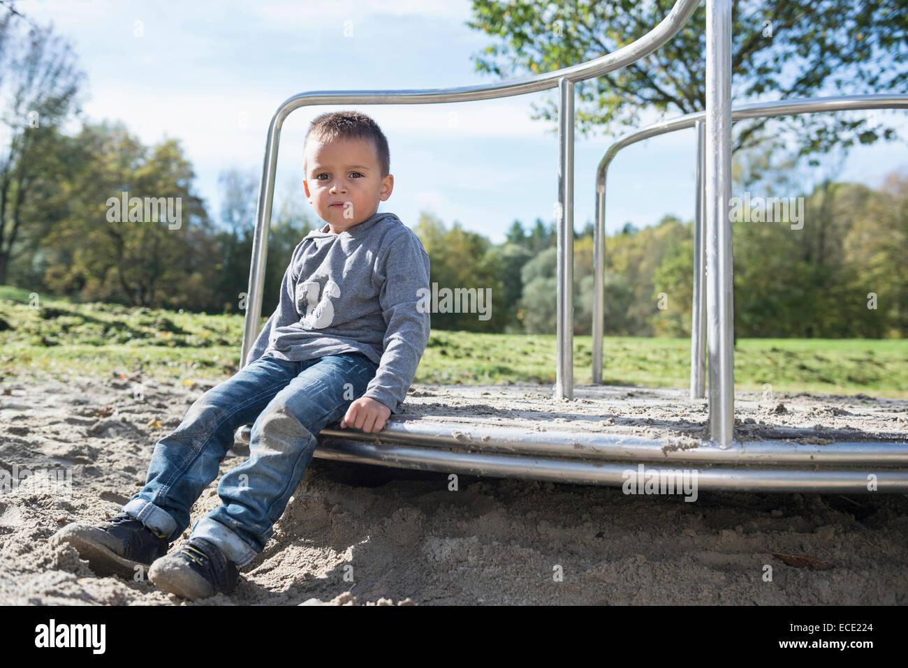 Boy playground sitting portrait sand carousel - Stock Image