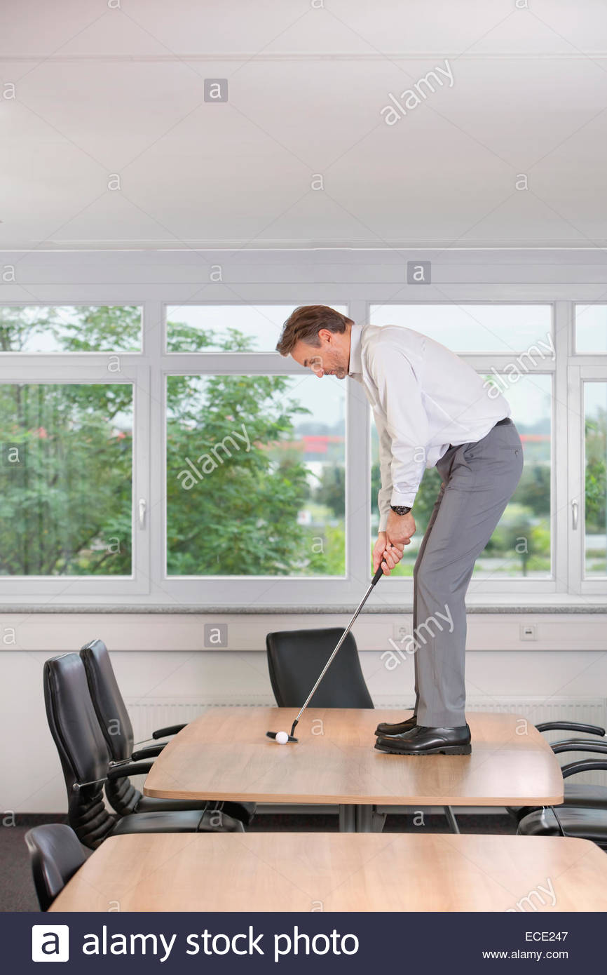 Office man concentrating Practising golf boss - Stock Image