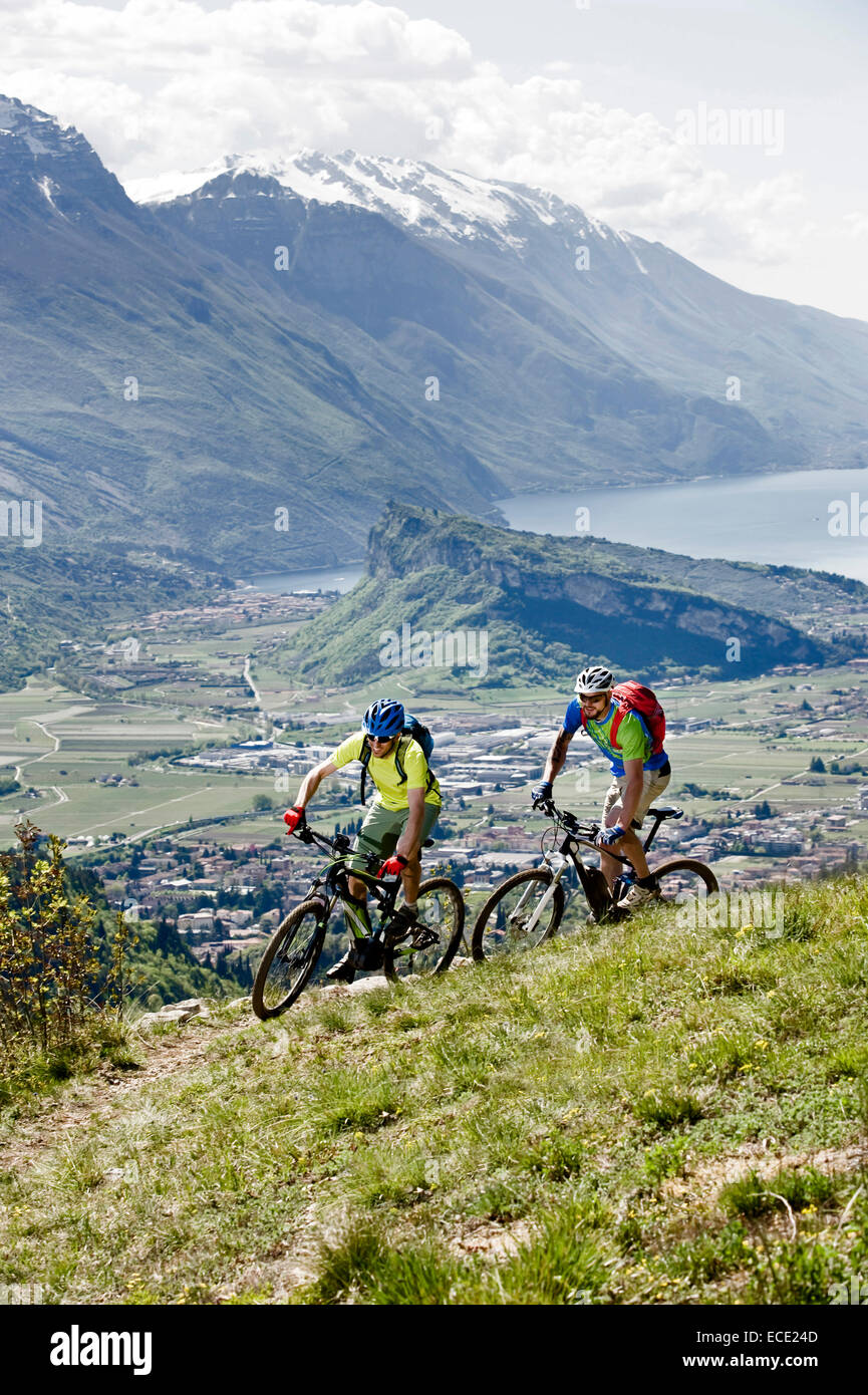 Men racing electic-mountainbikes cliff valley - Stock Image