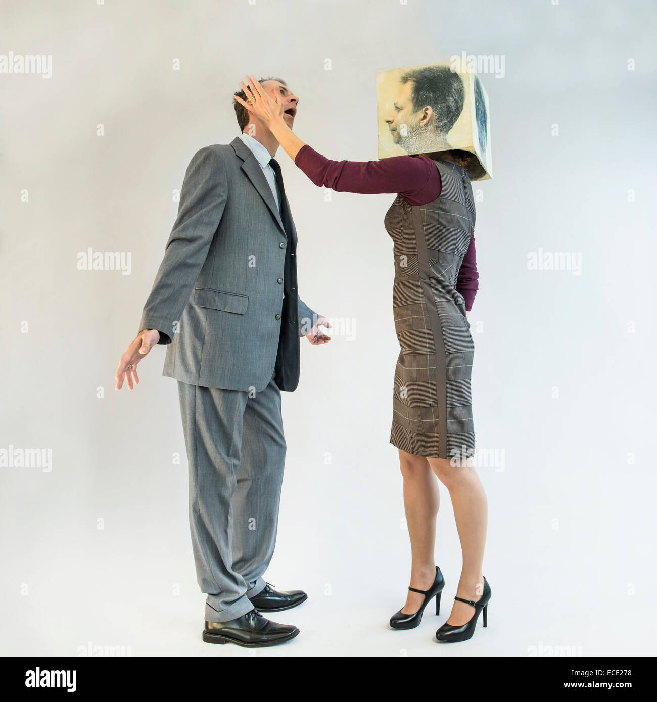 Businessman getting slapped by businesswoman wearing mask - Stock Image