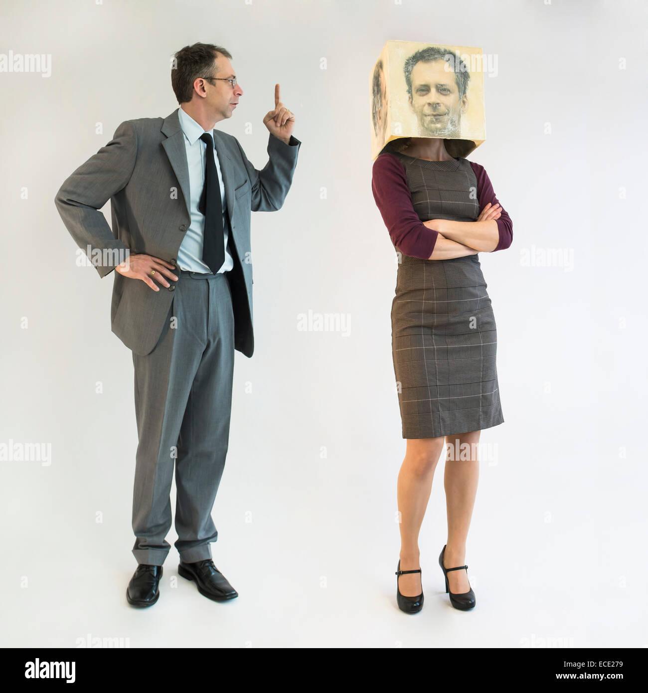 Businessman scolding businesswoman wearing mask - Stock Image