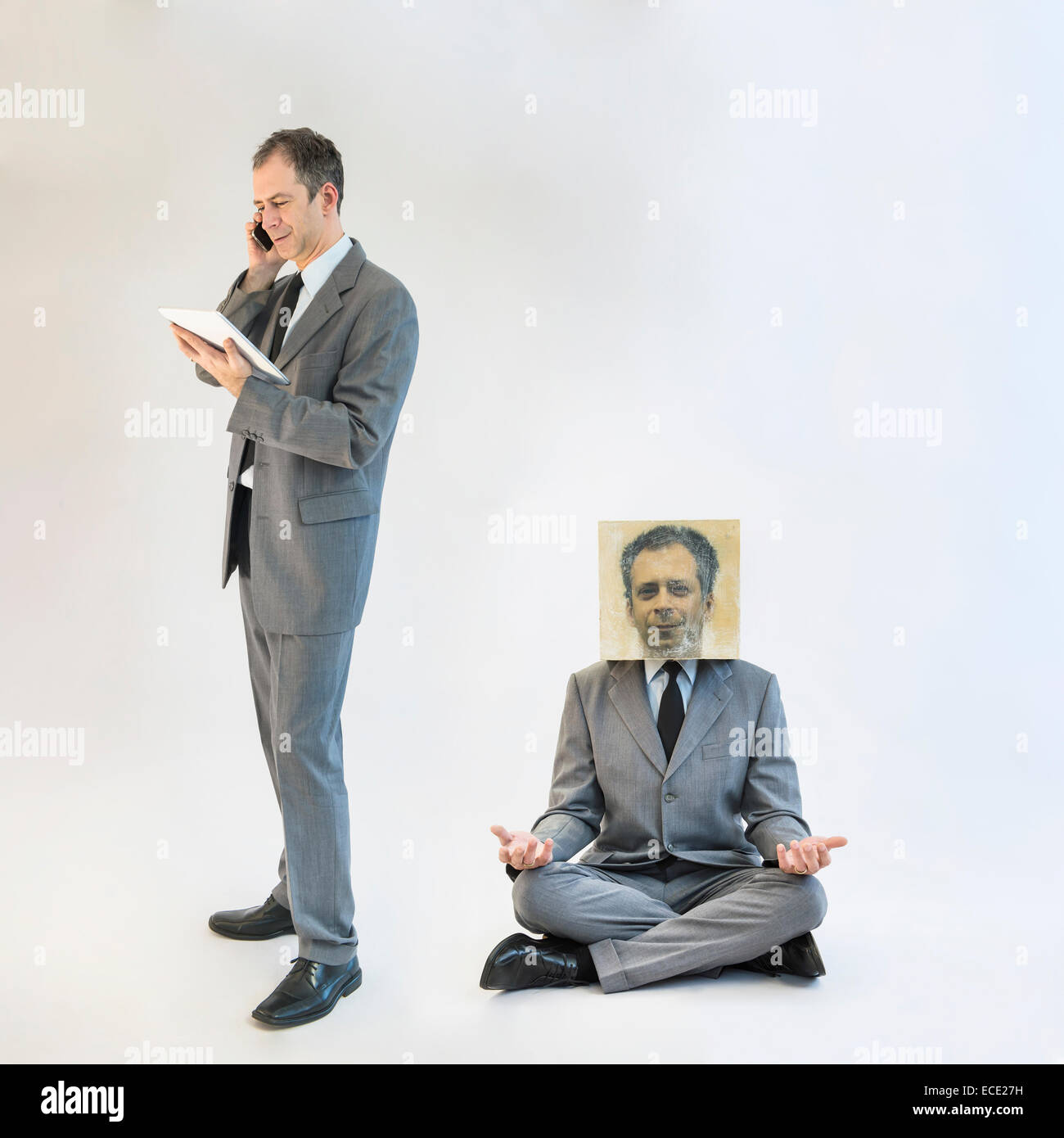 Businessman imagining self image of meditating while multitasking - Stock Image