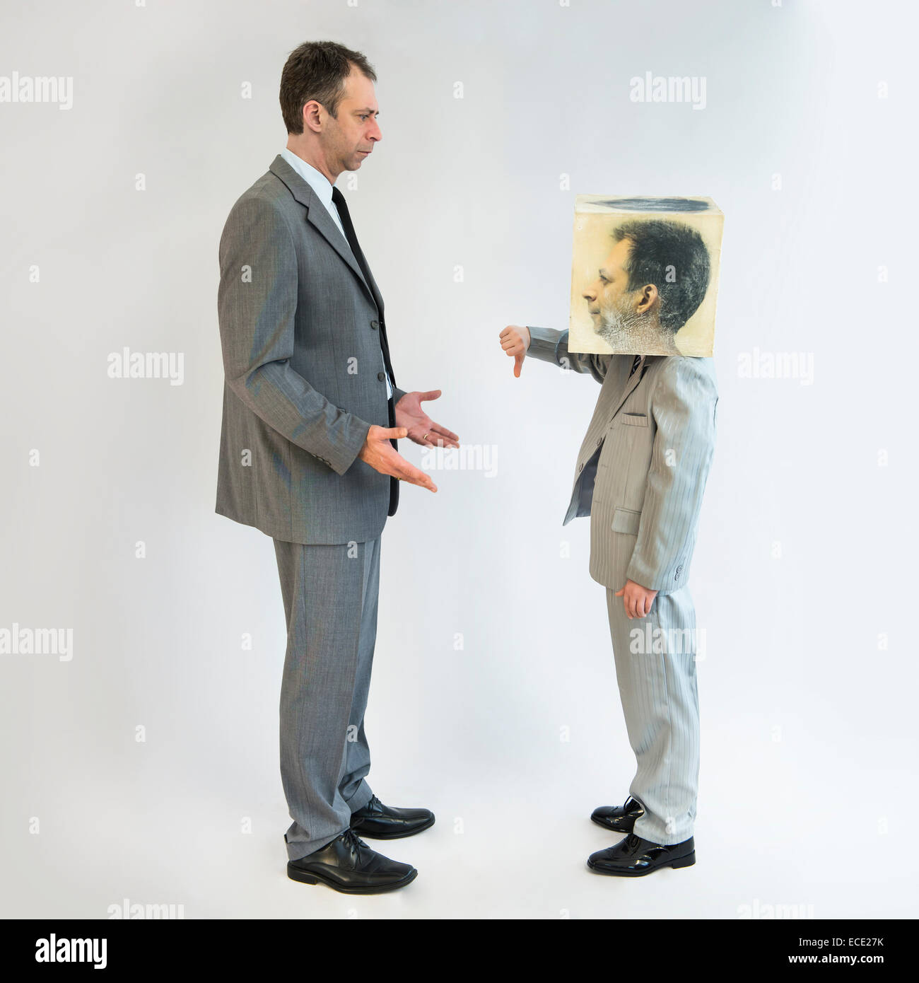 Boy wearing mask and showing thumbs down to businessman - Stock Image