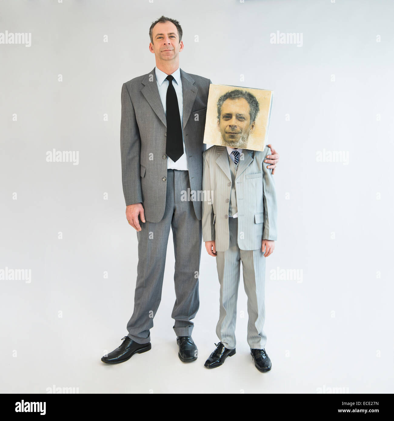 Businessman showing unity and standing near boy wearing mask - Stock Image