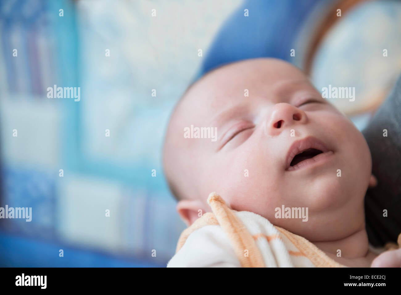Baby boy sleeping in arms of father, close up - Stock Image