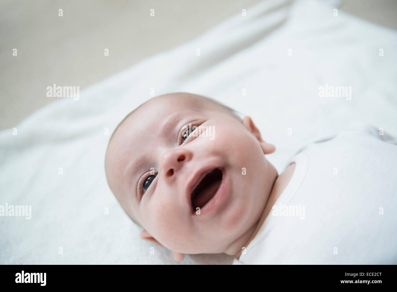 Baby boy lying on bed, smiling - Stock Image