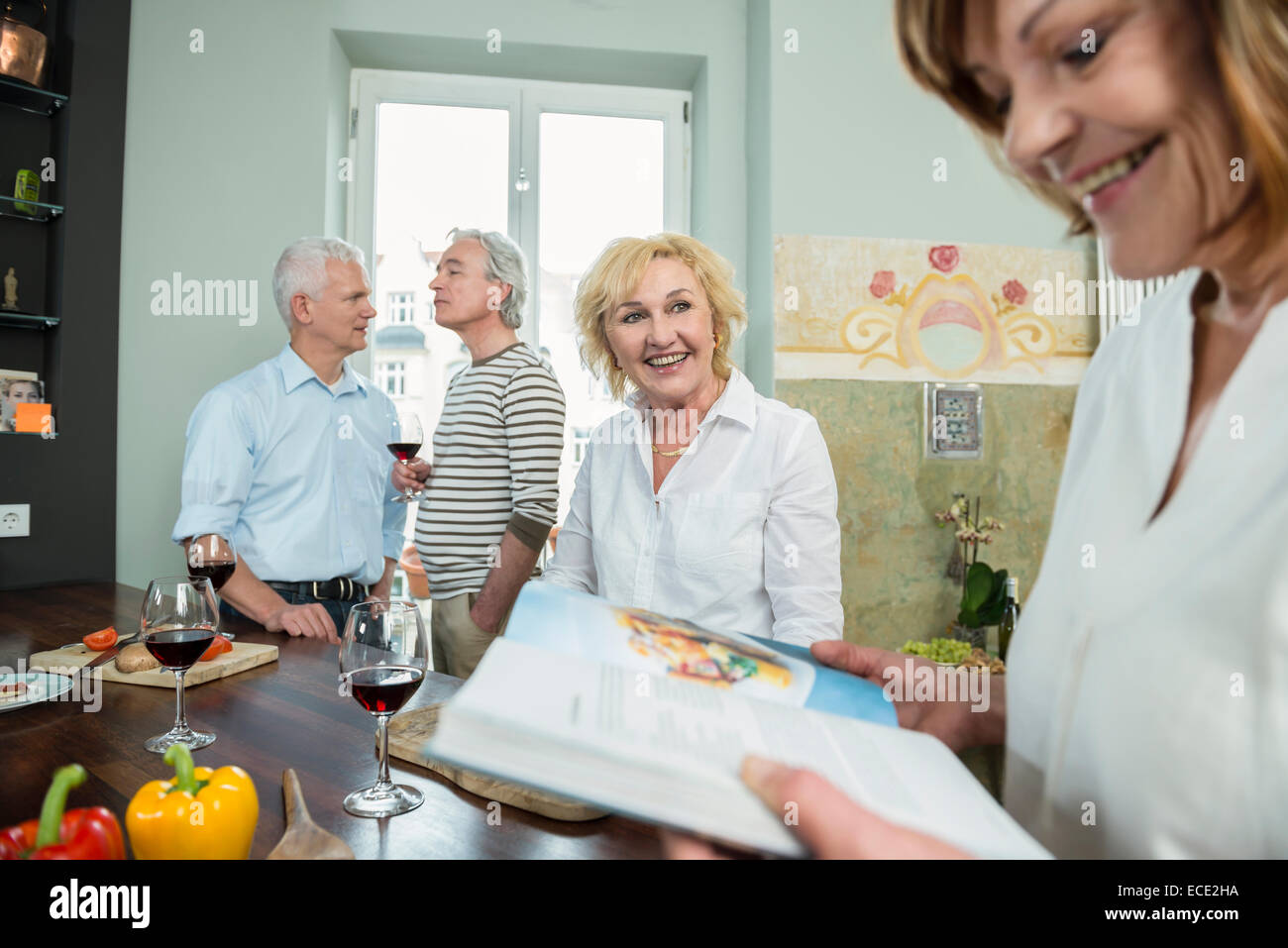 Senior group friends kitchen cooking drinking wine - Stock Image