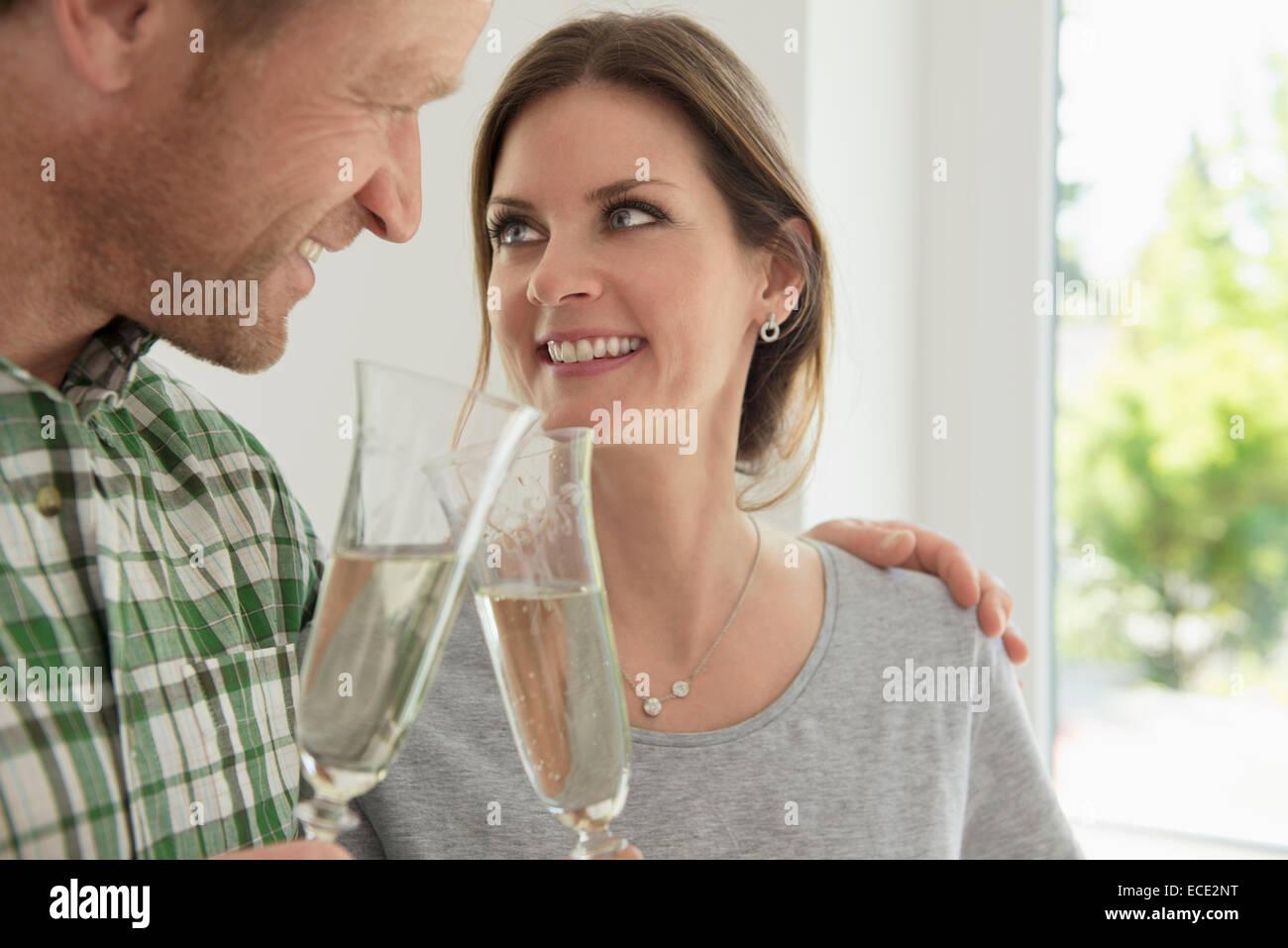 Couple celebrating drinking toasting new home - Stock Image