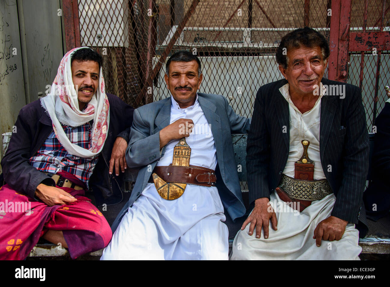 Men with their djambias sitting in front of a house in the old city, Sana'a, Yemen - Stock Image
