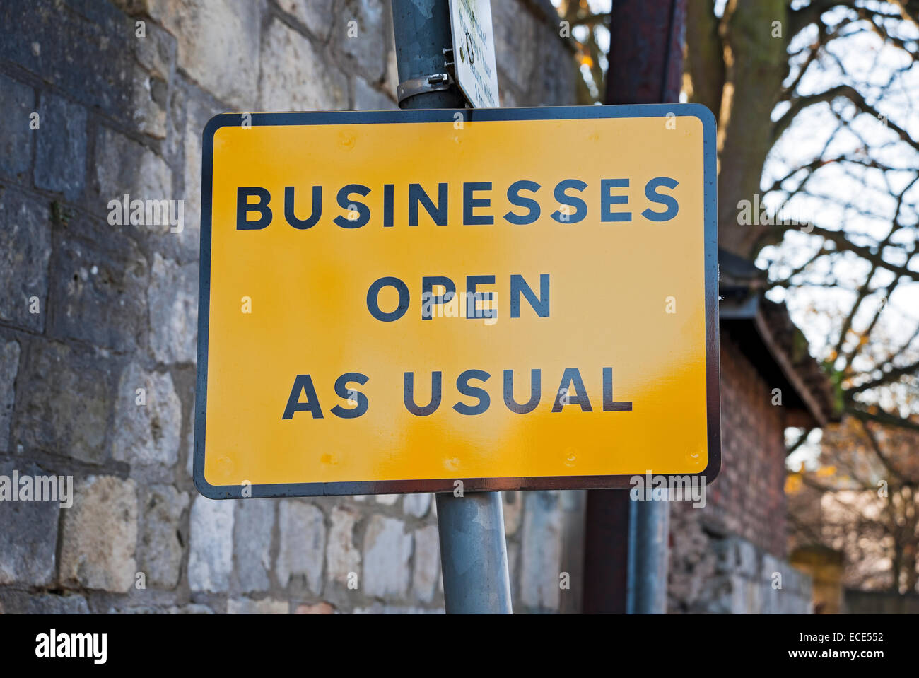 Businesses open as usual street sign England UK United Kingdom GB Great Britain - Stock Image