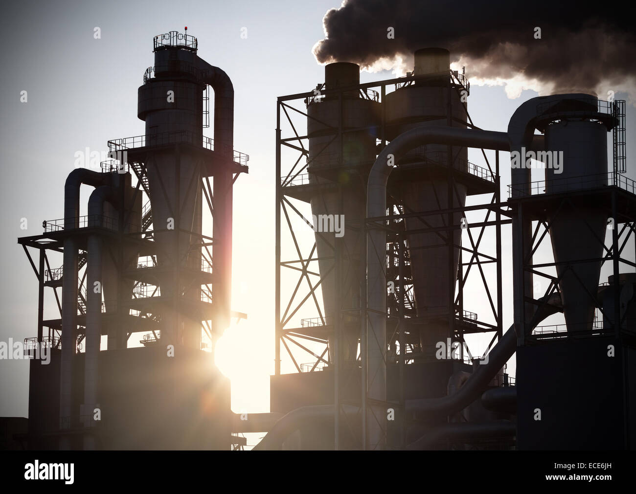 Smoky chimneys silhouettes against sun. Air pollution concept. - Stock Image