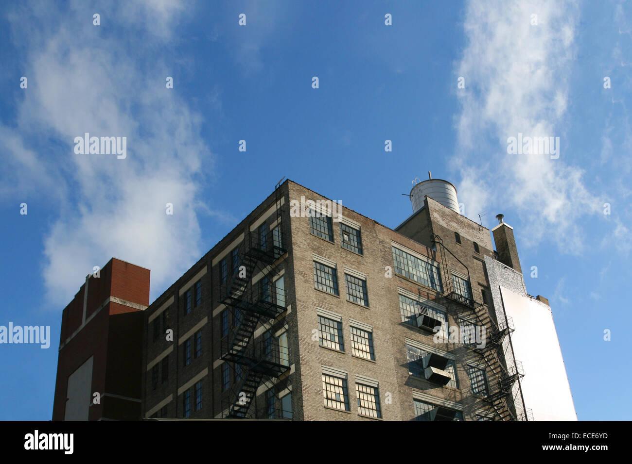 Backstein Gebaeude Feuerleiter Ziegel alt Himmel Freiraum Frei blau Industrie Haus Haeuser Fenster Bruechig bruechiges - Stock Image