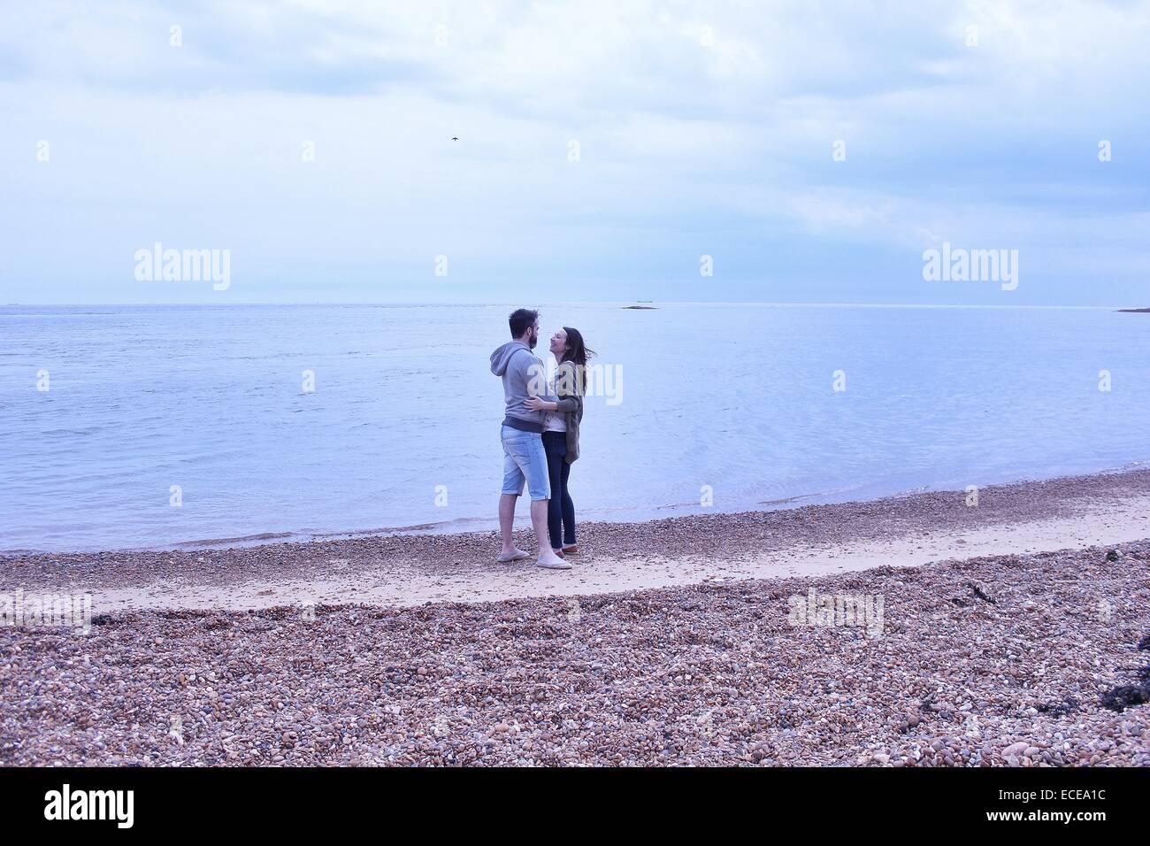 Couple standing on beach - Stock Image
