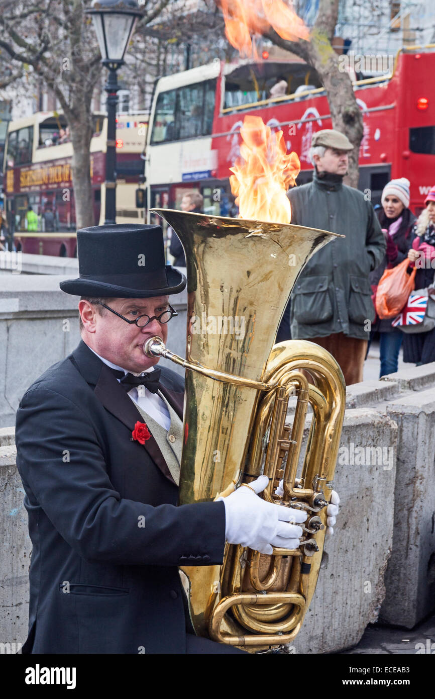 London, Trafalgar Square   A tuba-playing busker giving a new twist to the expression 'playing with fire' - Stock Image