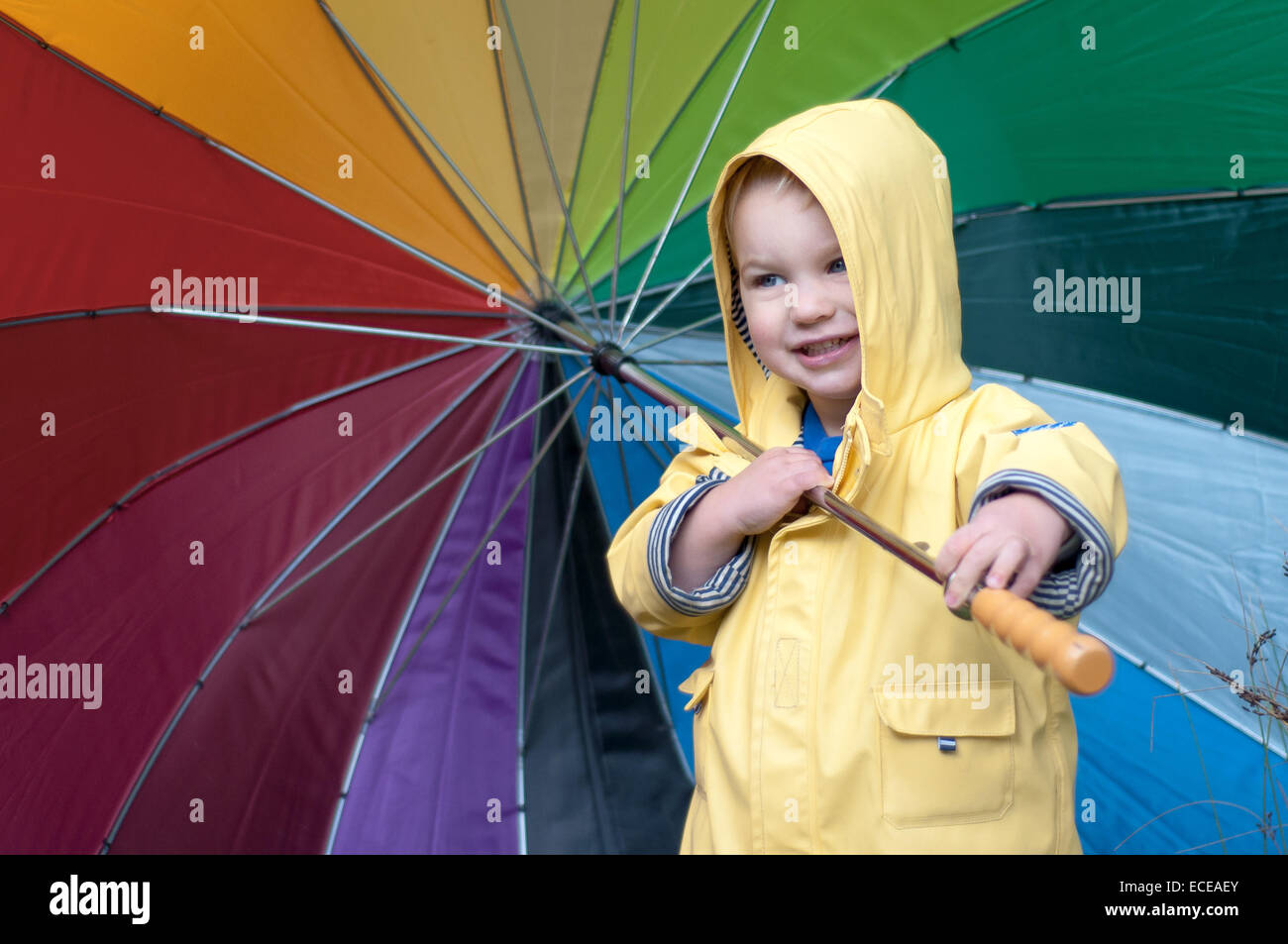 Boy in a rain coat holding multi-colored umbrella Stock Photo