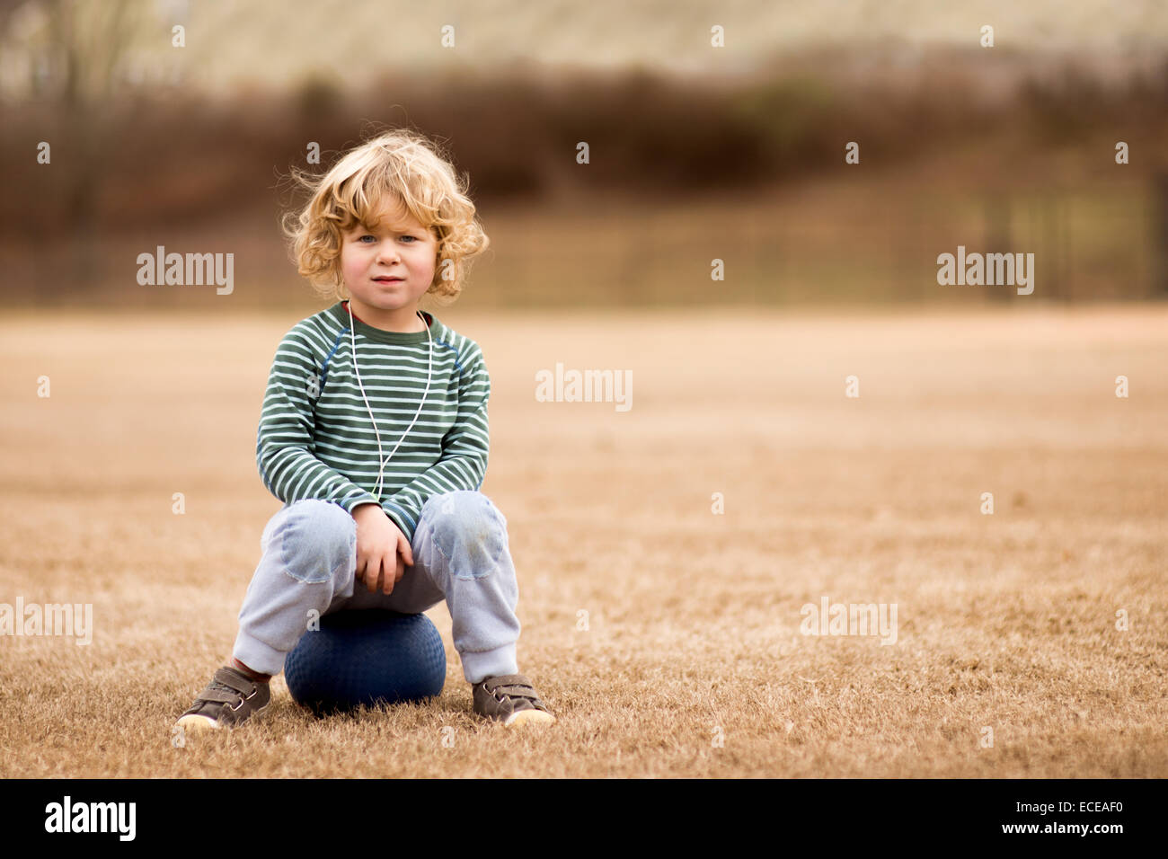 USA, South Carolina, Greenville County, Greenville, Boy (2-3) with ball in soccer field - Stock Image
