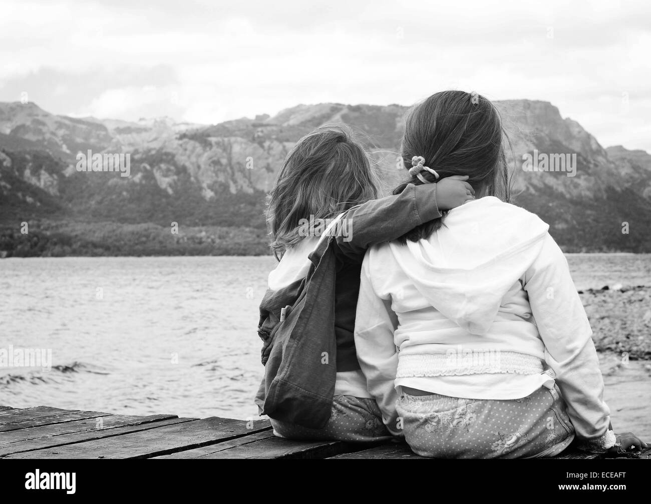 Argentina, Rio Negro, Sisters sitting on jetty by lake - Stock Image