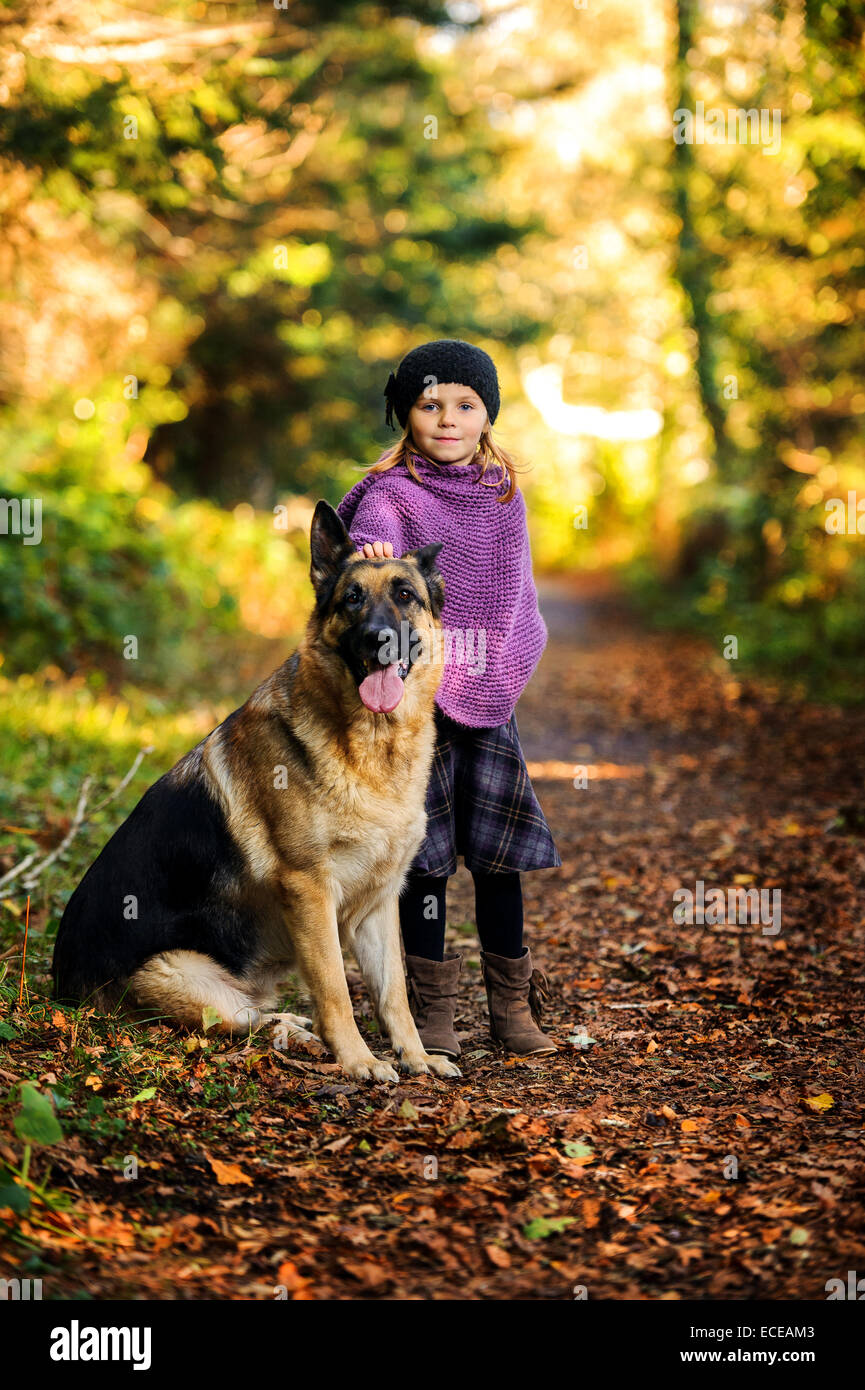 Young girl (2-3) with german shepherd in park - Stock Image